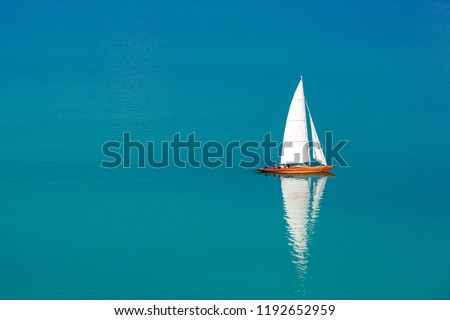 Perfect sailing background. Sailboat white sail and brown wooden boat in blue sea. Amazing recreational in nature concept design. Summer water sport, adventure outdoors Imagine de stoc ©