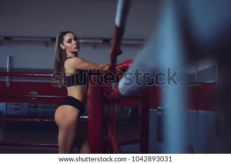Perfect sexual sport girl shows her ass into the camera and standing near boxing ring in boxing gloves. She looking at camera and smiling. Beginer model.
