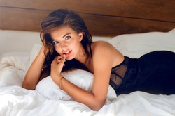 Perfect sexy tan woman with  perfect skin , big full lips posing at bedroom, wearing sexy luxury stylish  black lingerie.l Lady lying on her stomach on white bed.