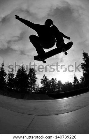 perfect silhouette of a skateboarder jumping high at the skate park.