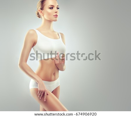 Perfect slim toned young body of the girl . An example of sports , fitness or plastic surgery and aesthetic cosmetology. Healthy Breast . #674906920