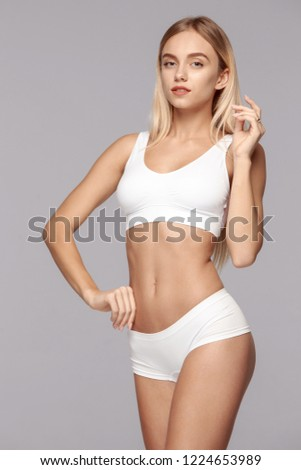 Perfect slim toned young body of the girl or fit woman at studio. The fitness, diet, sports, plastic surgery and aesthetic cosmetology concept. #1224653989