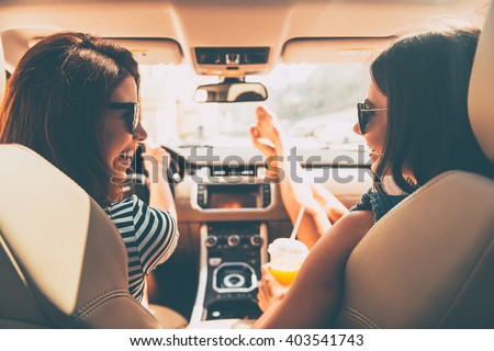Perfect start of holidays. Rear view of two beautiful young cheerful women looking at each other with smile while sitting in car