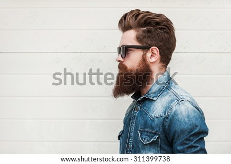 Perfect style. Side view of young bearded man in eyewear looking away while standing outdoors