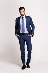 Perfect suit. Full length of handsome young man in suit looking at camera while standing against white background.