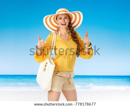 Perfect summer. happy active woman in shorts and yellow blouse with white beach bag on the beach showing thumbs up #778178677