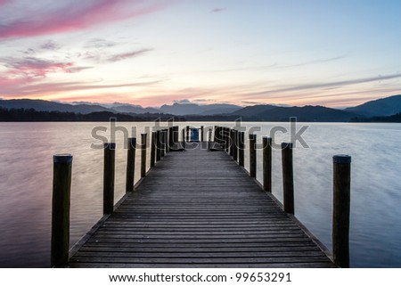 Perfect symmetry, a wooden jetty on Lake Windermere one tranquil spring evening with the Langdales in the background - Extra long exposure