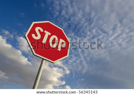 perfect texture of the surface of a stop sign against blue sky and white clouds