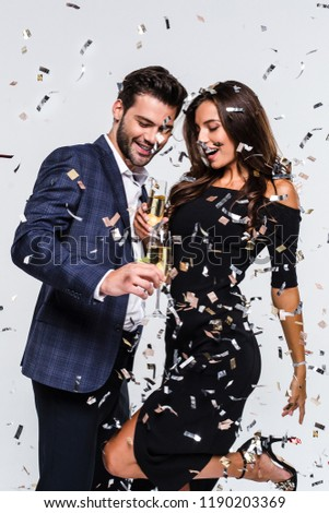 Perfect toast! Young beautiful couple bonding and dancing while standing against white background with confetti