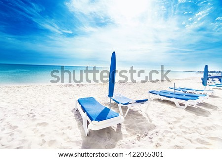 Perfect tropical paradise beach / Vacation holidays background wallpaper  with  beach lounge chairs and  tents