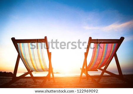 Perfect vacation concept: pair of beach loungers on the deserted coast sea at sunrise.