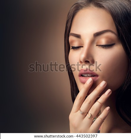 Perfect woman face portrait lips with fashion natural beige matte lipstick makeup. Beauty brunette sexy model girl with beautiful skin close her eyes and touching her lips.