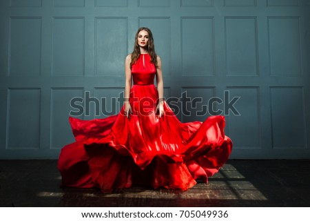 Perfect Woman in Red Dress. Beautiful Fashion Model on Blue Background #705049936