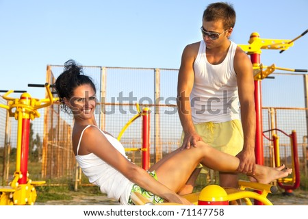 Perfect young model working out with her personal fitness trainer on fitness playground