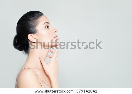 Perfect Young Woman Spa Model with Healthy Skin touching her Hand Her Face. Spa Beauty, Facial Treatment and Cosmetology Concept