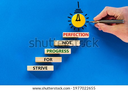 Perfection or progress symbol. Wooden blocks on blue background, copy space. Light bulb icon. Businessman hand with pen. Words 'Strive for progress not perfection'. Progress concept. Copy space.