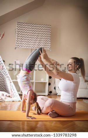 Perfectly balanced. Mother and daughter working exercise.