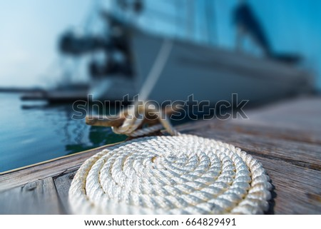 Perfectly coiled rope on the pier with secured yachts on the background