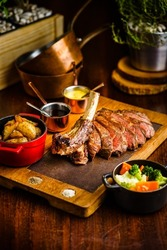 Perfectly cooked Dry Aged Tomahawk Wagyu beef steak with bone, vegetable side dish and gravy sauce on serving cast iron metal and wood pan over rustic kitchen background. Low key, dark warm tone light