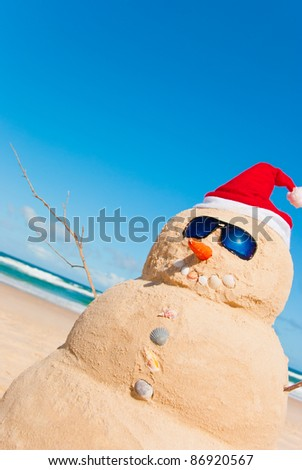 Perfectly Shaped Snowman made from sand whit santa hat and sunnies. There is loads of copy space for text in the sky