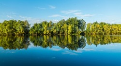 Perfectly smooth water surface on lake in the forest. Summer landscape. Glassy lake.
