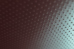 Perforated aluminum surface with many holes, hanging from above like a ceiling. Perforation rows go into the distance and form a perspective. Tinted red and green metal background. Dark wallpaper