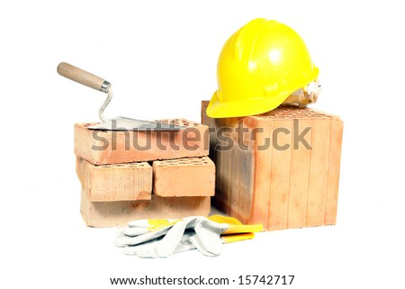 Perforated bricks, stainless steel trowel, yellow helmet and protective gloves isolated on white