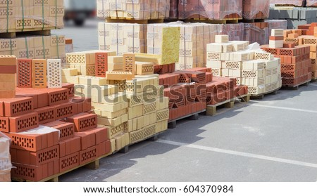 Perforated white, yellow and red bricks with a round and rectangular holes including decorative bricks on the wooden pallets on a warehouse outdoor