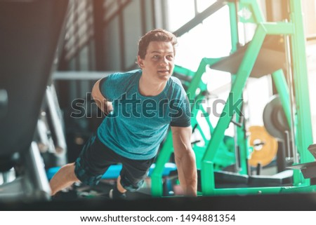 Perform better, be better. Young man in sportswear exercising indoors. Copy space in upper left part #1494881354