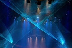 Performance moving LED Par lighting on construction light beam ray downward in blue color with Laser smoke graphic, on Concert and Fashion Show stage ramp, low light exposure with grain and noise