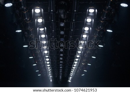 Performance moving lighting luminous rays on construction light beam ray downward in white color, on Concert and Fashion Show stage ramp