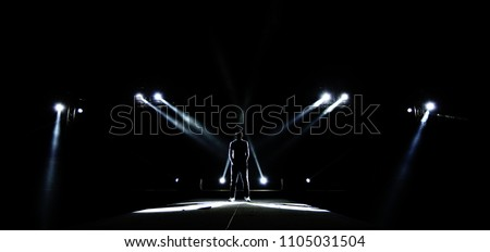 Performance moving lighting on construction light beam ray downward to Man on Stage as Leader Superstar, Silhouette of Male surround with Light, Dark Low Exposure, concept Unique Confidence