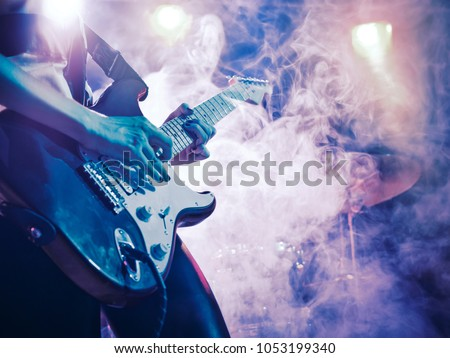 Performance of the rock band. The guitarist plays solo. The bass player plays solo. Drummer. Bass drum. Close-up. #1053199340