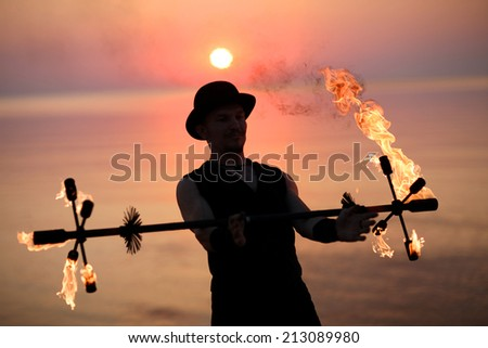 Performer with a burning torch; special equipment for fire show