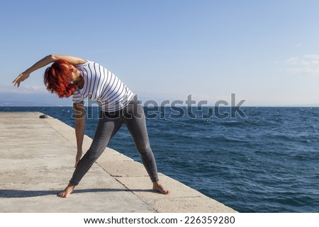 Performing Joga on windy day. Cute woman meditating, performing joga on sea coast, windy sunny day, high, rough sea in the background