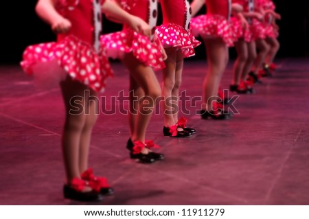 Performing on stage, a group of young dancers show off their talent and bright costumes - image highlights a narrow depth of field on the girl in the middle of the line