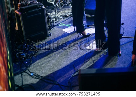 Performs a musical group on stage, on the floor sheet with songs, wires and shoes. #753271495