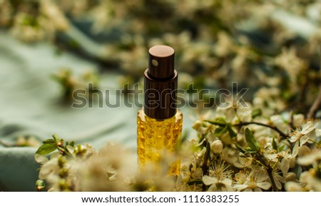 perfume and aromatic oils bottles surrounded by fresh flower  #1116383255