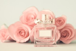 Perfume bottle in front of pink roses