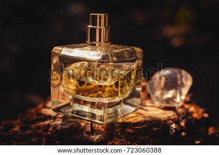 Perfume bottle on wooden surface against black background