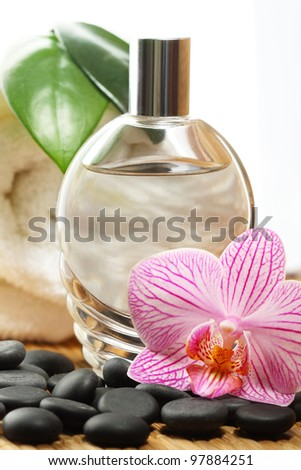 Perfume bottle, orchid flower and white towel.