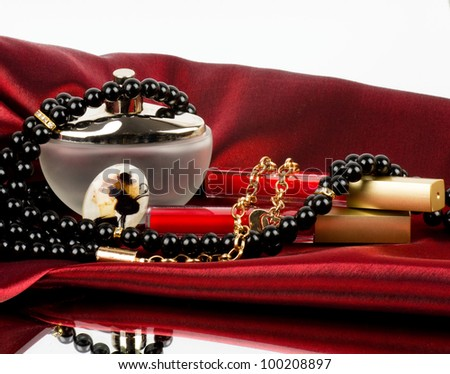 Perfume bottle, red lipstick and pearls beads