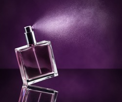 perfume bottle spraying on dark purple background