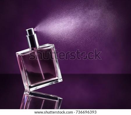 perfume bottle spraying on dark purple background