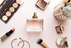 Perfume bottle with makeup cosmetics on pink dressing table. Scent fragrance cosmetic beauty product. Beauty blogger concept. Flat lay.