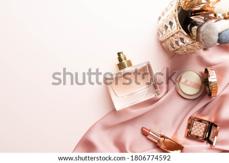 Perfume bottle with makeup cosmetics on pink silk folded fabric background. Scent fragrance cosmetic beauty product. Flat lay.