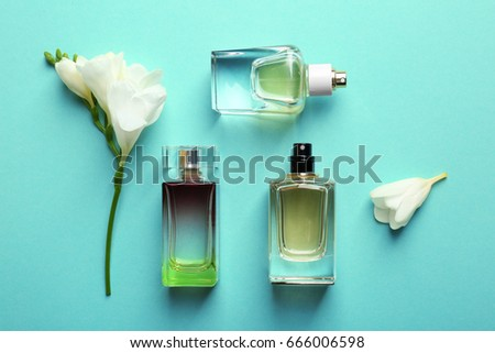 Perfume bottles on mint background, top view