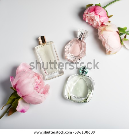 Perfume bottles with flowers on light background. Perfumery, cosmetics, fragrance collection. Flat lay #596138639
