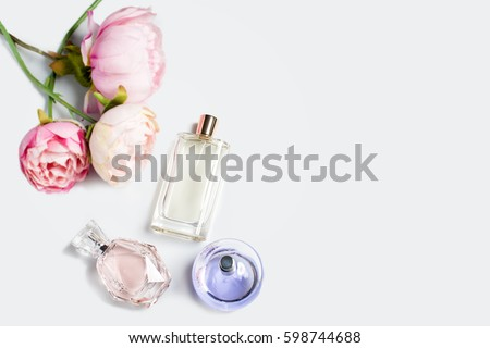 Perfume bottles with flowers on light background. Perfumery, cosmetics, fragrance collection. Free space for text. #598744688