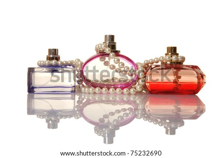 Perfume in a glass bottles and pearl beeds on white background